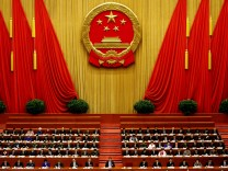FILE PHOTO:  China's President Xi Jinping and other delegates listen as China's Premier Li Keqiang (not pictured) delivers a government work report during the opening session of the National People's Congress at the Great Hall of the People in Beijing