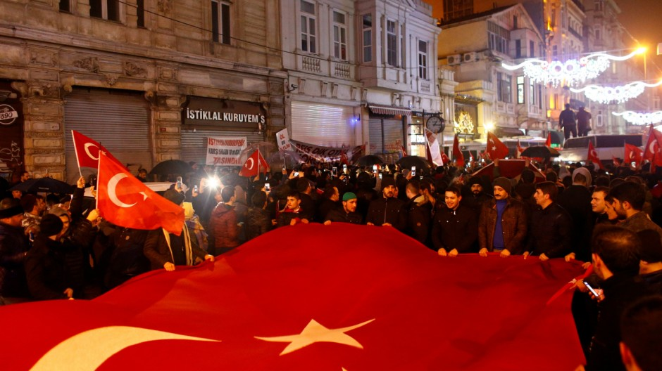 People wave Turkish flags during a protest in front of the Dutch Consulate in Istanbul