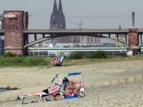 Sommerhitze in Köln am Rhein Personen mit Liegestühle n sonnen sich am Rheinufer in den Poller Auen