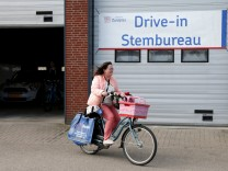 A cyclist leaves a drive-in polling station after voting in the Dutch general election in Zuidplas