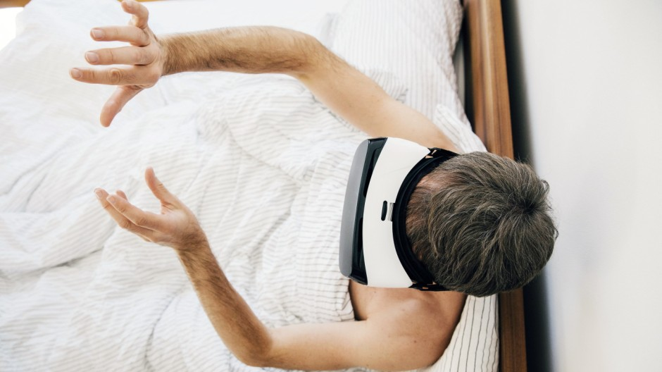 Man in bed wearing virtual reality glasses moving his hands model released Symbolfoto property relea