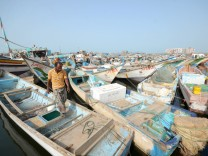 FILE PHOTO - A fisherman walks on a boat docked at the Red Sea port of Hodeidah