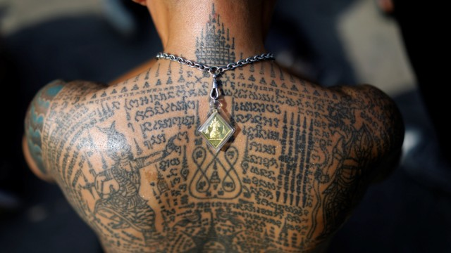 A devotee attends the religious tattoo festival at Wat Bang Phra where they come to recharge the power of their sacred tattoos in Nakhon Pathom province