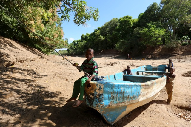 FILE PHOTO: Children play on an abandoned boat along the Shabelle River bed, which is dry due to drought in Somalia's Shabelle region