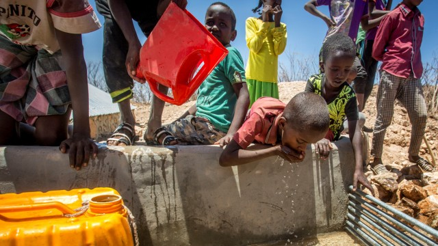 Children drink water delivered by a truck in the drought-stricken Baligubadle village
