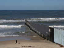 A woman runs next to a section of the wall separating Mexico and the United States, in Tijuana