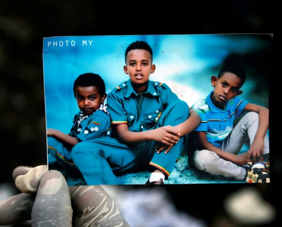 A rescue worker holds a photograph of children suspected to be missing at a pile of garbage following a landslide when a mound of trash collapsed on an informal settlement at the Koshe garbage dump in Ethiopia's capital Addis Ababa