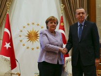 Turkish President Erdogan and German Chancellor Merkel exchange a handshake in Ankara