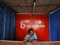 FILE PHOTO: A retail shop owner speaks on his mobile phone outside his closed shop shutters painted with an advertisement for Vodafone at a market in Chennai