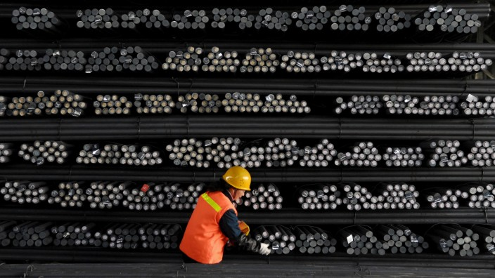 A labourer marks steel bars at a steel and iron factory in Huai'an