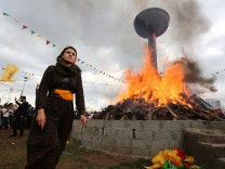 A woman walks past a bonfire during a gathering celebrating Newroz, which marks the arrival of spring and the new year, in the Kurdish-dominated southeastern city of Diyarbakir