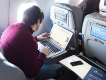 Journalists use their computers to test a new high speed inflight Internet service named Fli-Fi while on a special JetBlue media flight out of John F. Kennedy International Airport in New York