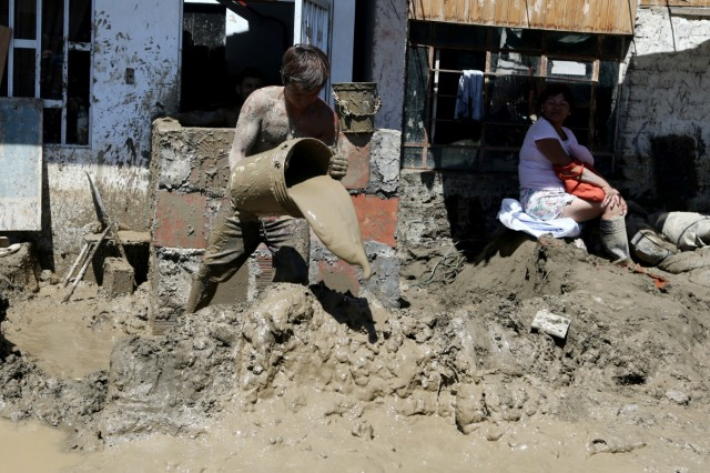 A man cleans a flooded home after rivers breached their banks due to torrential rains, causing flooding and widespread destruction, in Huarmey
