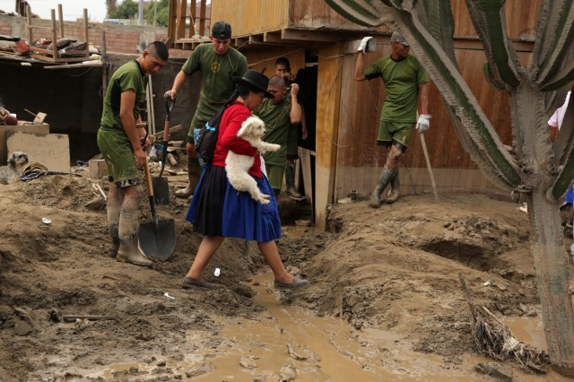 A woman carrying a dog walk past a flooded street, after rivers breached their banks due to torrential rains, causing flooding and widespread destruction in Huachipa, Lima
