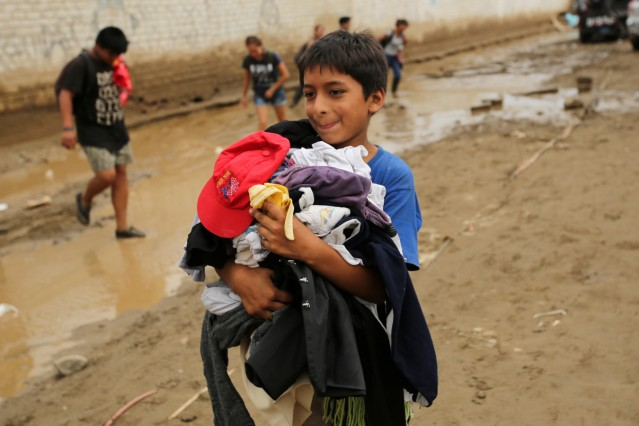 A child carries donated clothes, after rivers breached their banks due to torrential rains, causing flooding and widespread destruction in Cajamarquilla, Lima