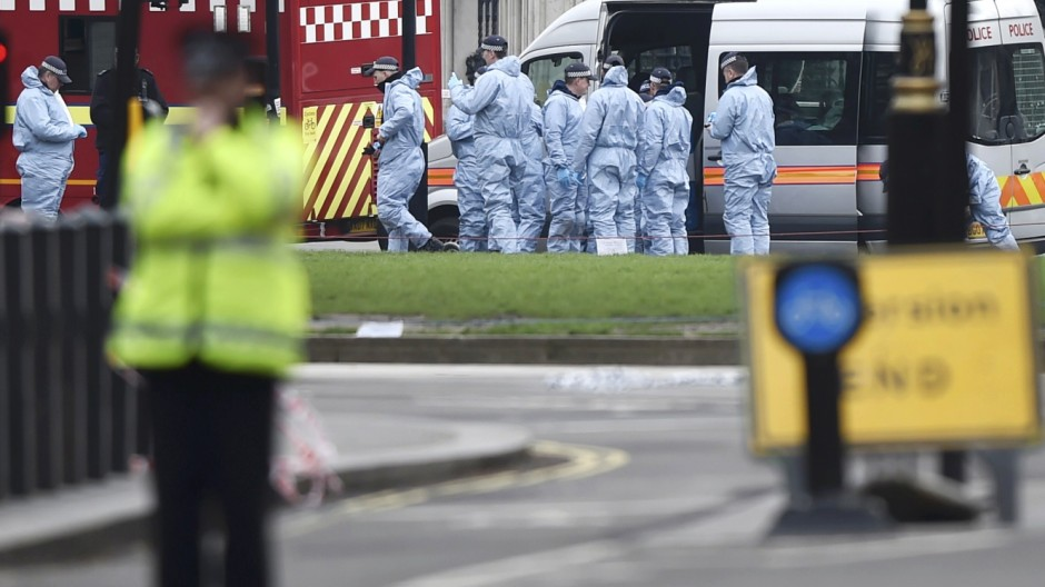 Police officers work in Westminster the morning after an attack in London