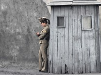 A female North Korean soldier uses her mobile phone next to a sentry on the banks of the Yalu River, near the North Korean town of Sinuiju