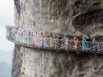 Women wearing cheongsam pose for pictures on a walkway along a cliff during an event in Chongqing Municipality