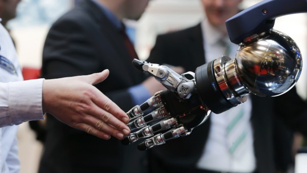A woman reaches out to shake hands with a robotic hand at the booth of Schunk at the world's largest industrial technology fair, the Hannover Messe, in Hanover