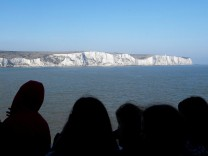 Passengers view the white cliffs of Dover from a cross-channel ferry between Dover in Britain and Calais in France