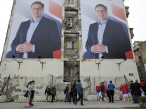 People pass posters of Serbian PM Vucic, in Novi Sad