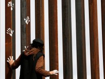 Activist paints the U.S.-Mexico border wall between Ciudad Juarez and New Mexico as a symbol of protest against U.S. President Donald Trump's new immigration reform in Ciudad Juarez, Mexico