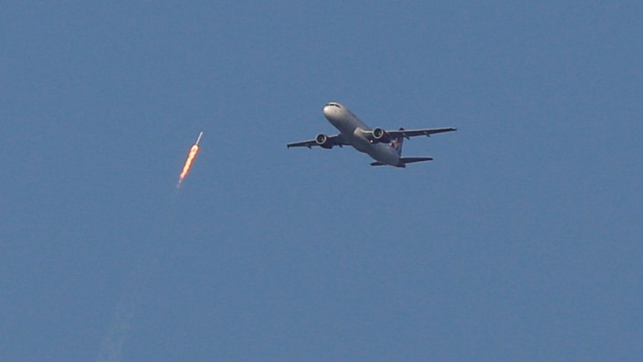 A recycled SpaceX Falcon 9 rocket soars toward space above a Virgin Airlines passenger jet, which had just departed Orlando International Airport, in Orlando