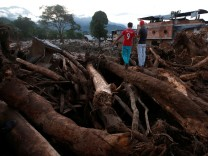 Men look at a destroyed area afterwards heavy rains caused several rivers to overflow, pushing sediment and rocks into buildings and roads in Mocoa