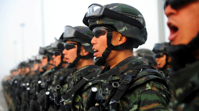 FILE PHOTO: Paramilitary policemen stand in formation as they take part in an anti-terrorism oath-taking rally, in Kashgar