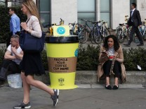 A woman sits next to a new coffee cup recycling point in the City of London