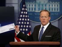 White House Press Secretary Sean Spicer shows a check from U.S. President Donald Trump's salary which will be donated to the National Park Service during a daily press briefing at the White House in Washington