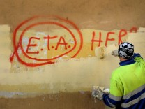 FILE PHOTO: A municipal worker paints over graffiti reading 'ETA, The People Are With You' in the Basque town of Guernica
