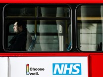 FILE PHOTO:  A man sits on a bus with an advertisement for Britain's National Health Service (NHS) in London