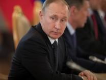 Russian President Vladimir Putin listens to Uzbek President Shavkat Mirziyoyev during their talks in Moscow's Kremlin
