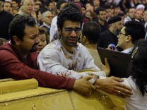 Relatives of victims react next to coffins arriving to the Coptic church that was bombed on Sunday in Tanta