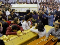 Relatives of victims react to coffins arriving to the Coptic church that was bombed on Sunday in Tanta