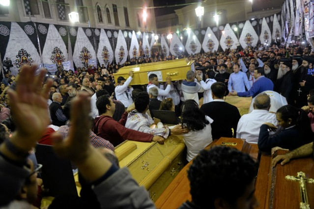 Mourners carry the coffins of victims into the Coptic church that was bombed on Sunday in Tanta, Egypt