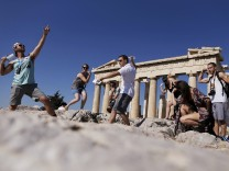 A group of tourists takes a selfie in front of the temple of the Parthenon atop the Acropolis in Athens