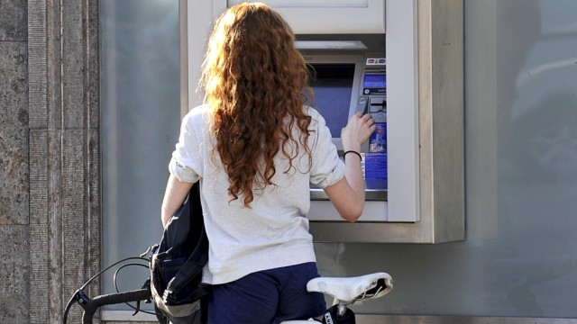 Frau mit Rennrad am Geldautomat