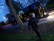 Police with the Borussia Dortmund team bus after an explosion near their hotel before the game