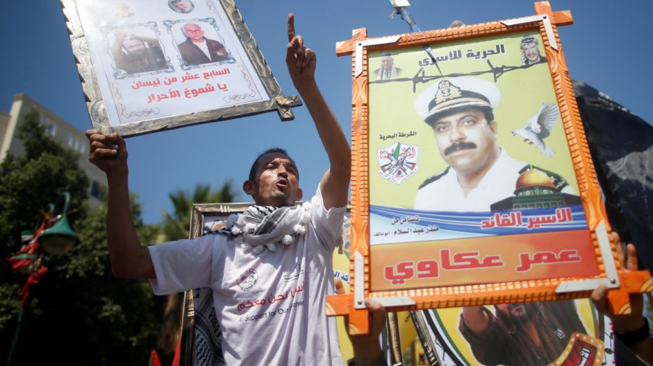 Demonstrators hold pictures of jailed Palestinians during a rally in support of Palestinian prisoners on hunger strike in Israeli jails, in Gaza City