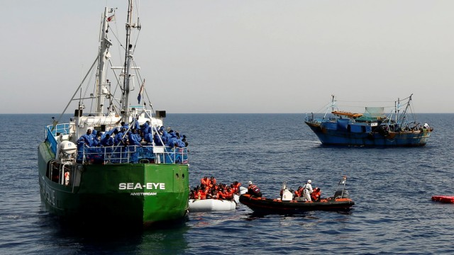 A Spanish military aircraft flies overhead as rescue NGOs Sea-Eye, Migrant Offshore Aid Station (MOAS) and Jugend Rettet Iuventa, and a Tunisian fishing boat carry out a joint rescue operation as some 20 migrants drowned in the central Mediterranean