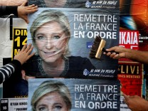 FILE PHOTO: Members of the French National Front (FN) political party paste a poster on a free billboard for the French National Front political party leader Marine Le Pen in Antibes