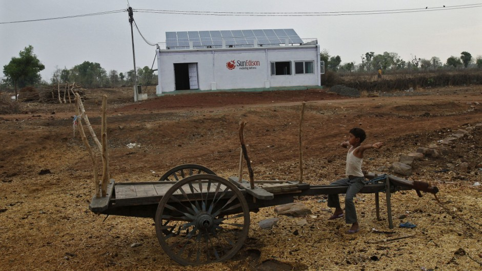 A boy sits on a cart in front of a solar power plant at Meerwada village of Guna district in the central Indian state of Madhya Pradesh