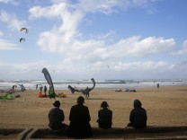 Ultra-Orthodox Jewish men watch people kite surfing in the Mediterranean sea in Tel Aviv