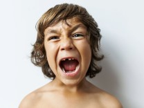 Portrait of screaming little boy with tooth gap in front of white background model released Symbolfo
