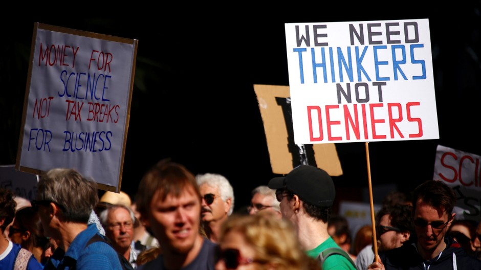 Protesters hold placards and banners as they participate in the March for Science rally on Earth Day, in central Sydney
