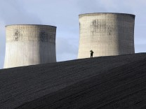 A security guard watches from a coal heap during a climate change protest at Ratcliffe Power Station at Ratcliffe-on-Soar