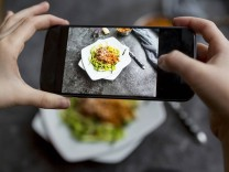 Girl taking a photo zoodles with vegetarian bolognese sauce with her smartphone close up model rele