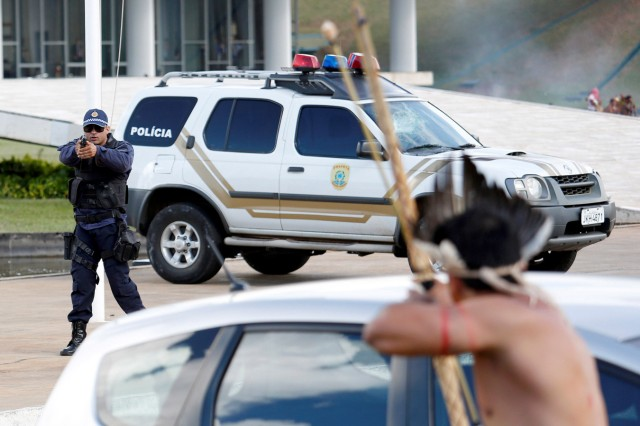 Riot police points his gun at Brazilian Indians during a demonstration against the violation of indigenous people's rights, in Brasilia
